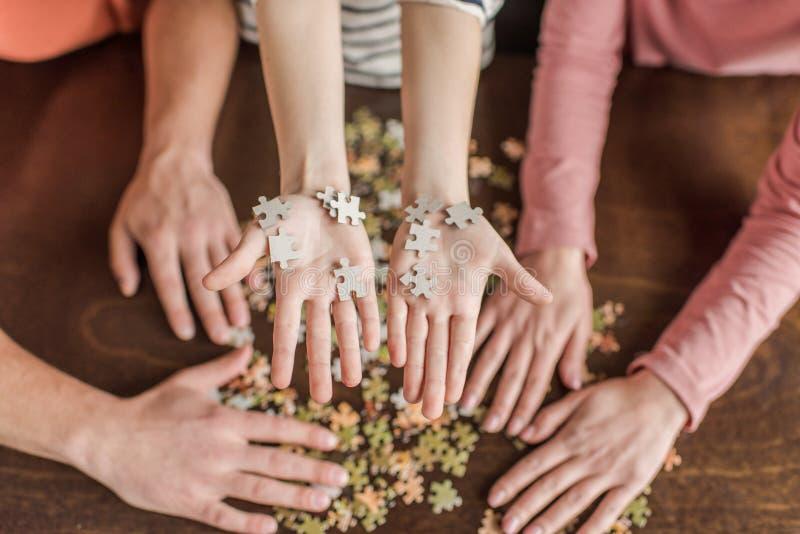 Rodzina z jeden dzieckiem bawić się z łamigłówkami na stole fotografia royalty free
