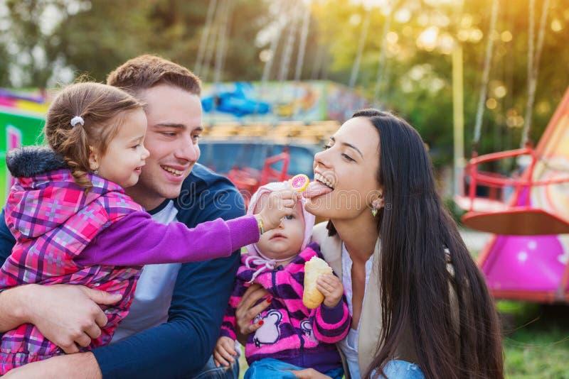 Rodzina z małymi dziewczynkami cieszy się czas przy zabawa jarmarkiem fotografia stock