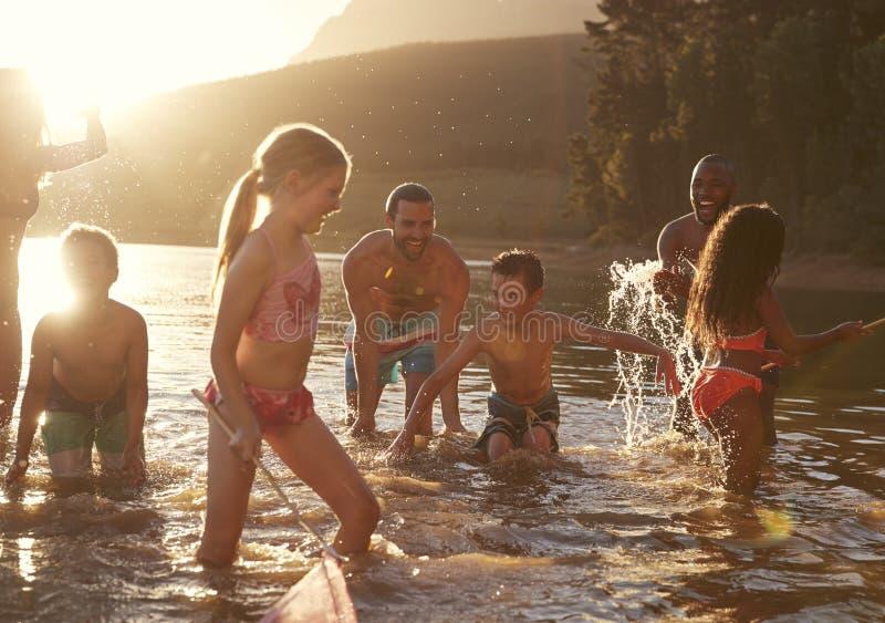 Rodzina Z przyjaciółmi Cieszy się wieczór pływanie W Wieś jeziorze obraz royalty free