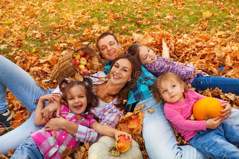 Rodzina z trzy dziewczynami kłaść w liściach klonowych fotografia stock