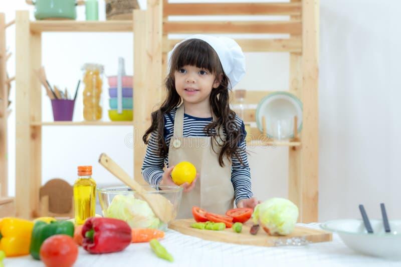 rodzina zdrowa Żartuje dziewczyny kucharstwo i tnących warzywa dla zdrowej opieki na kuchni Córka robi ciastku, w ten sposób szcz fotografia royalty free