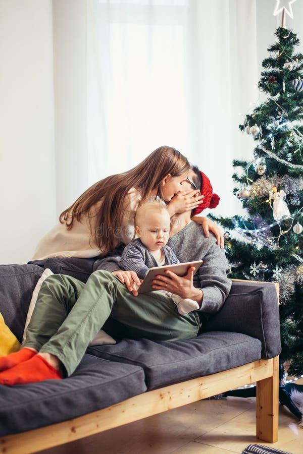 Rodzina znajduje cyfrową pastylkę w prezencie na Bożenarodzeniowej nocy, blisko drewnianej kuchenki obrazy stock