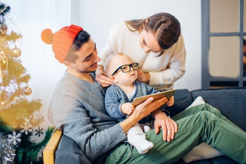 Rodzina znajduje cyfrową pastylkę w prezencie na Bożenarodzeniowej nocy, blisko drewnianej kuchenki obraz royalty free