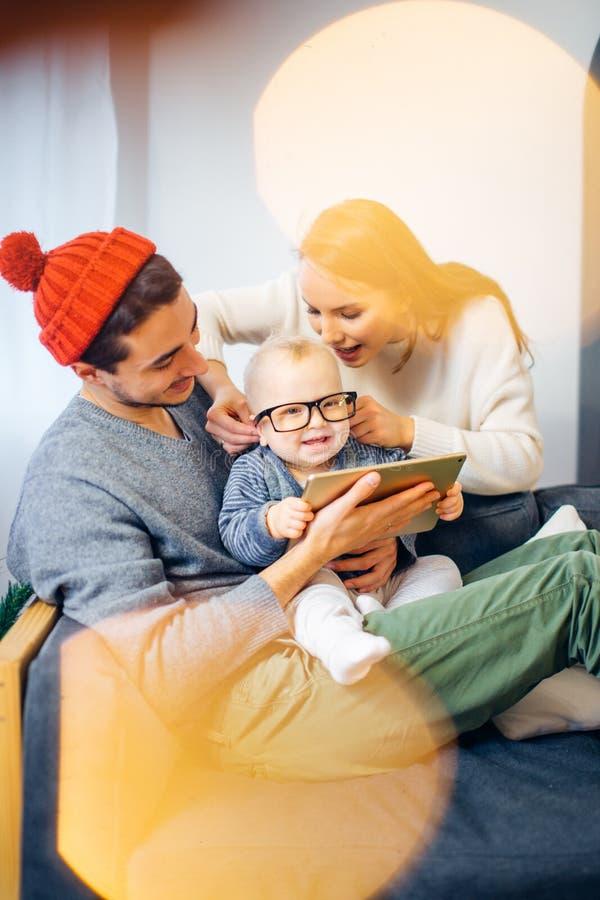 Rodzina znajduje cyfrową pastylkę w prezencie na Bożenarodzeniowej nocy, blisko drewnianej kuchenki zdjęcia royalty free