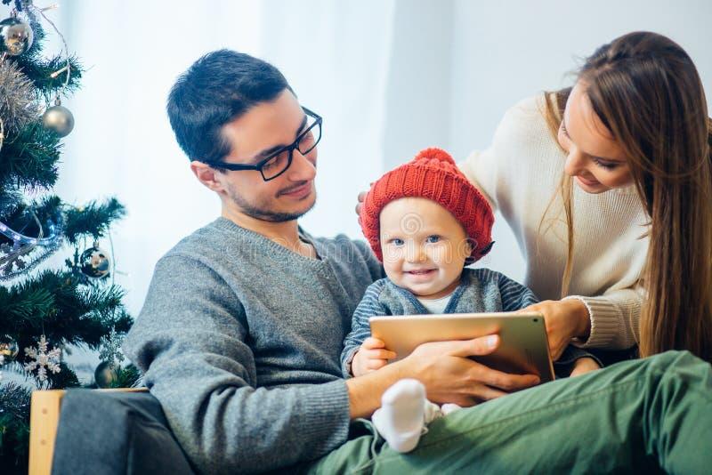 Rodzina znajduje cyfrową pastylkę w prezencie na Bożenarodzeniowej nocy, blisko drewnianej kuchenki fotografia royalty free