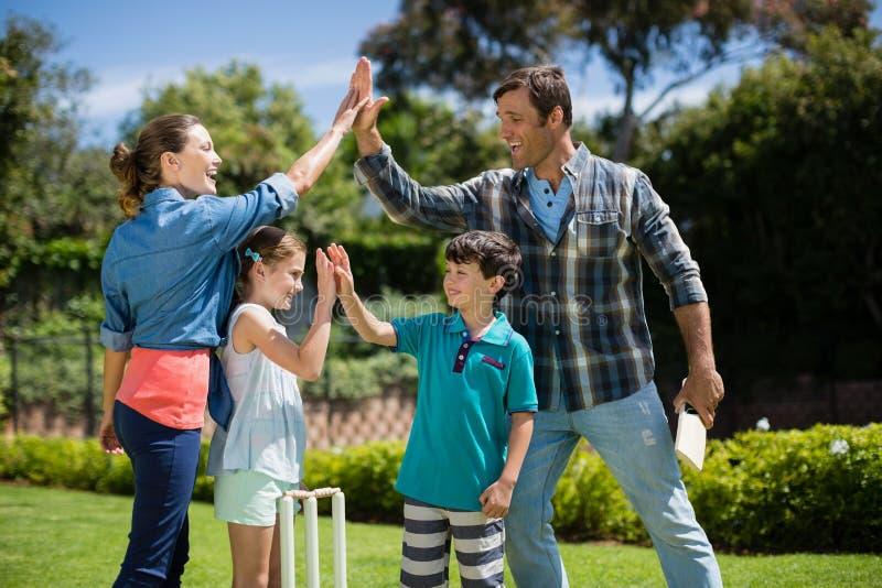Rodzinna daje wysokość pięć each inny podczas gdy bawić się krykieta obraz royalty free