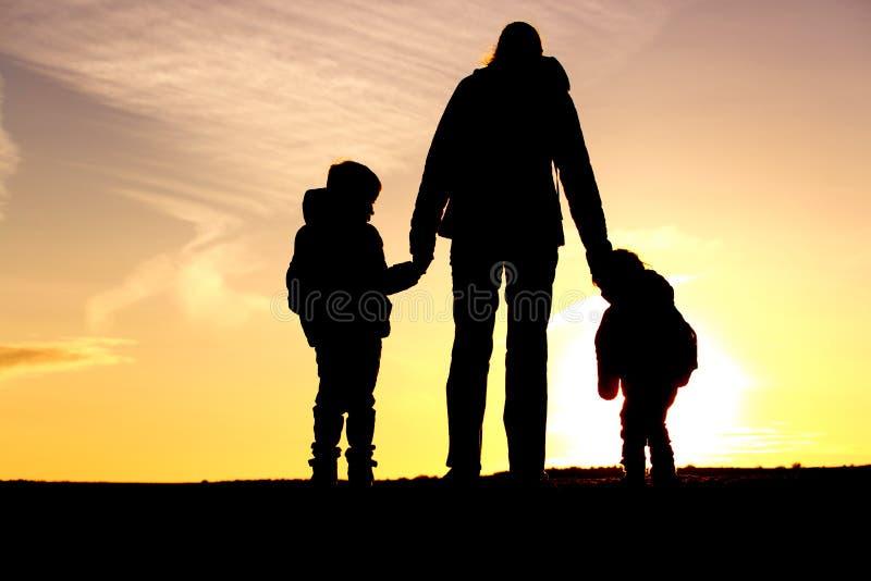 Rodzinna podróż matka i dwa dzieciaka z plecakami przy zmierzchem - obraz stock