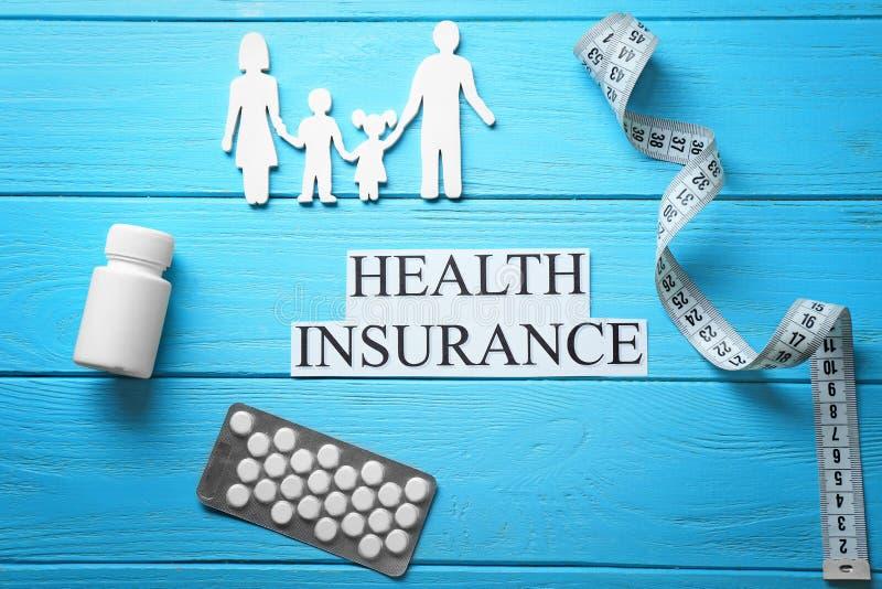 Rodzinna postać, pigułki, pomiarowa taśma i zwrota ubezpieczenie zdrowotne na drewnianym tle, zdjęcie stock