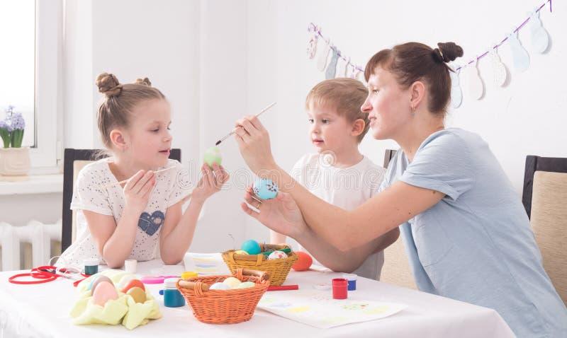 Rodzinna wakacyjna wielkanoc: Matka pomaga jej córki malować Wielkanocnego jajko fotografia royalty free
