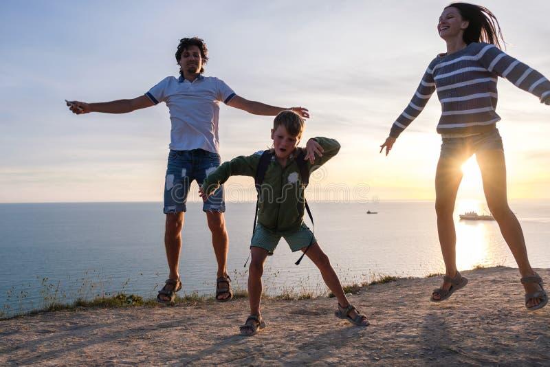 Rodzinna zabawy rozrywka na górze z nadmorski widokiem Tata, mama i syn, skaczemy przy zmierzchem Boczny widok obrazy stock