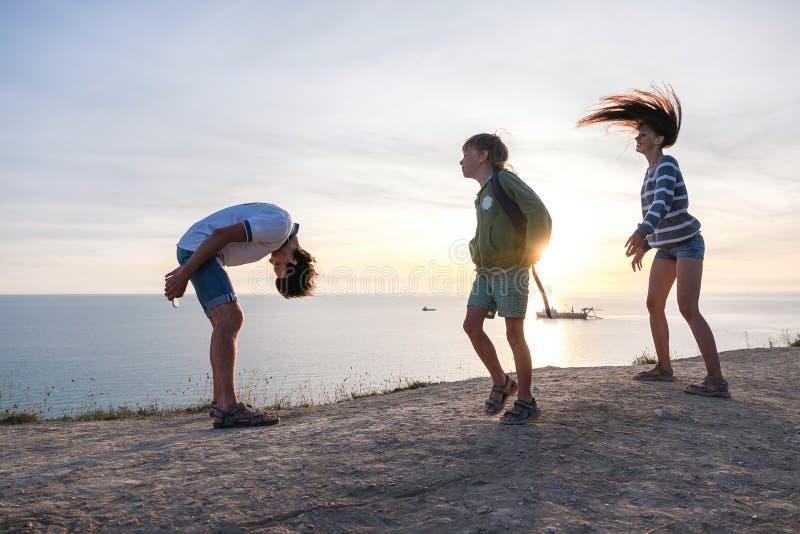 Rodzinna zabawy rozrywka na górze z nadmorski widokiem Tata, mama i syna taniec przy zmierzchem, Boczny widok zdjęcia royalty free