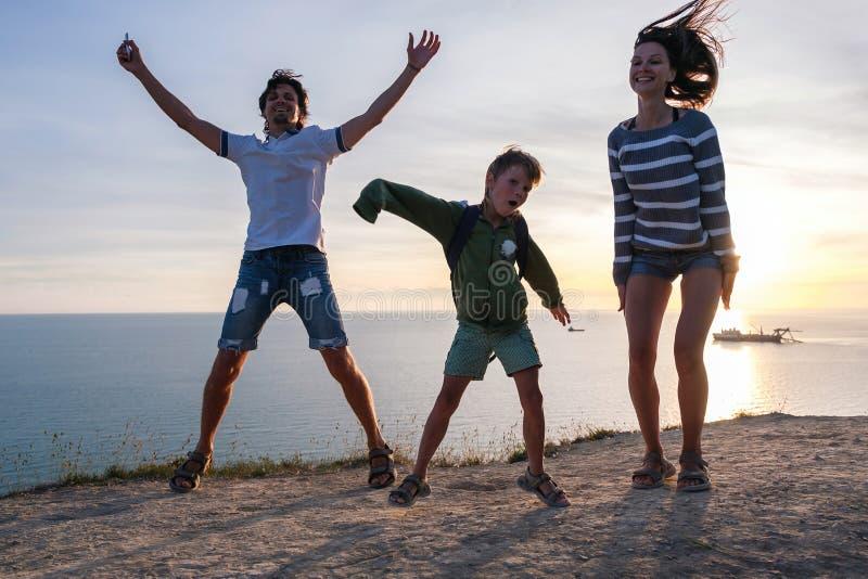 Rodzinna zabawy rozrywka na górze z nadmorski widokiem Tata, mama i syna taniec przy zmierzchem, Frontowy widok obraz royalty free