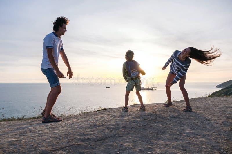 Rodzinna zabawy rozrywka na górze z nadmorski widokiem Tata, mama i syna taniec wpólnie przy zmierzchem, obraz stock