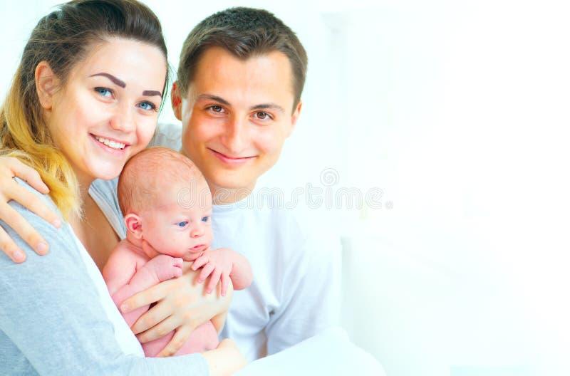 rodzinne tła ojca dziecka szczęśliwa matka odizolowana w białych smile young Ojciec, matka i ich nowonarodzony dziecko, obraz stock