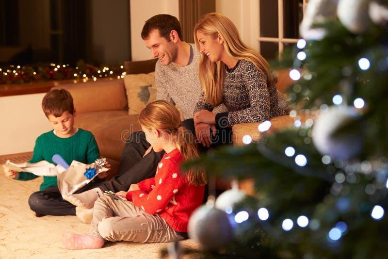 Rodzinni rozpakowywanie prezenty choinką zdjęcia royalty free