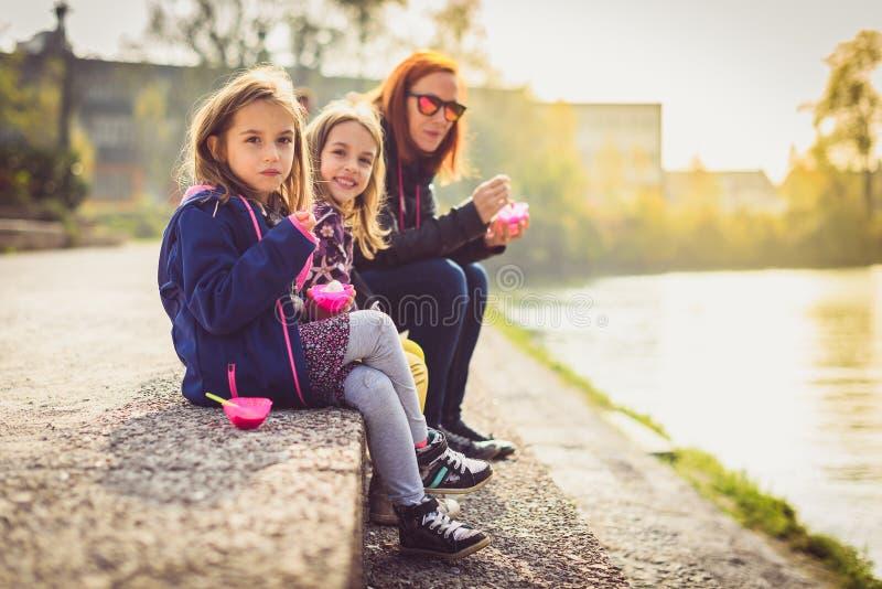 Rodzinny łasowanie lody, siedzi na bankach rzeczny Ljubljanica obrazy stock