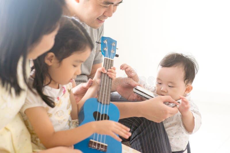 Rodzinny bawić się ukulele i harmonijka w domu zdjęcie stock