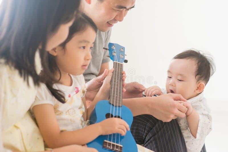Rodzinny bawić się ukulele w domu zdjęcia stock