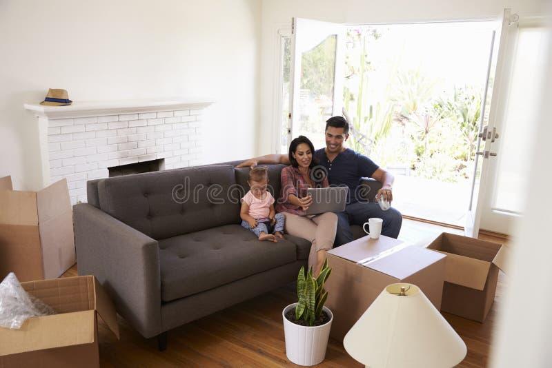 Rodzinny Bierze przerwę Na kanapie Używać laptop Na Poruszającym dniu fotografia royalty free