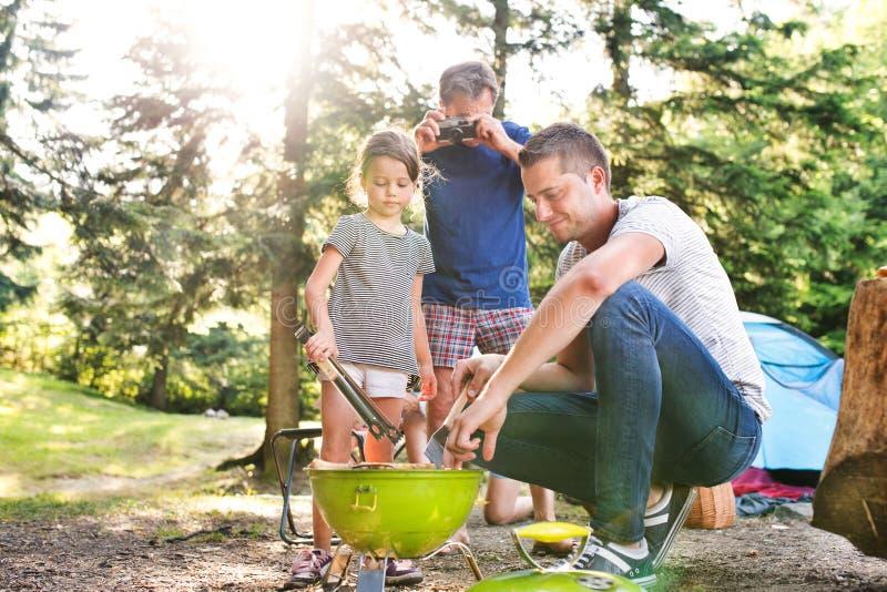 Rodzinny camping w lesie, kulinarny mięso na grilla grillu obraz stock