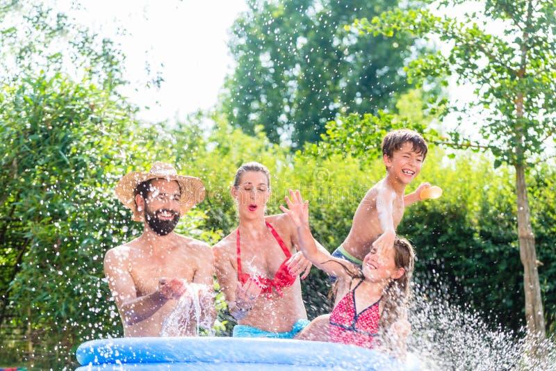 Rodzinny chłodniczy puszek bryzga wodę w ogrodowym basenie fotografia stock