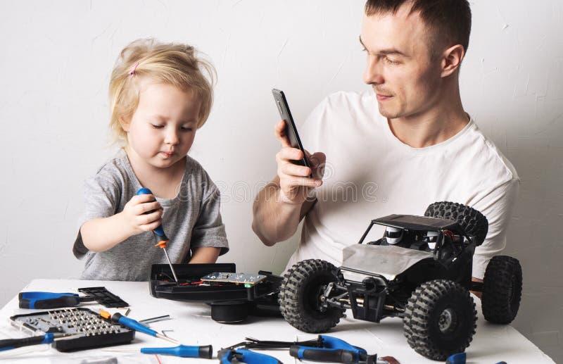 Rodzinny czas: Córka z ojcem naprawia kontrolującego powozika modela Tata strzela remontowego proces na jego smartphone zdjęcie stock