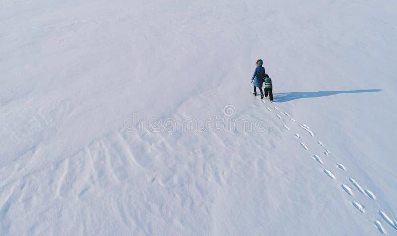 Rodzinny czasu spacer, sztuka i wpólnie Matka i syn biega ręka w rękę przez śniegu zakrywaliśmy teren w zimie plecy obrazy royalty free