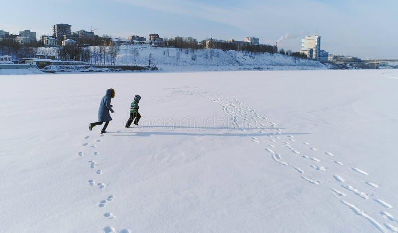 Rodzinny czasu spacer, sztuka i wpólnie Matka i syn biega ręka w rękę przez śniegu zakrywaliśmy teren w zimie plecy fotografia stock