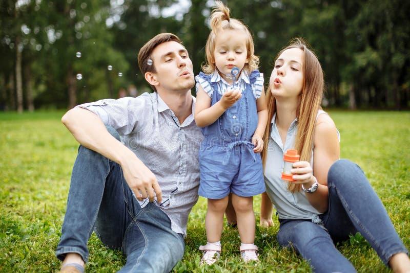 Rodzinny dmuchanie gulgocze w parku zdjęcie stock