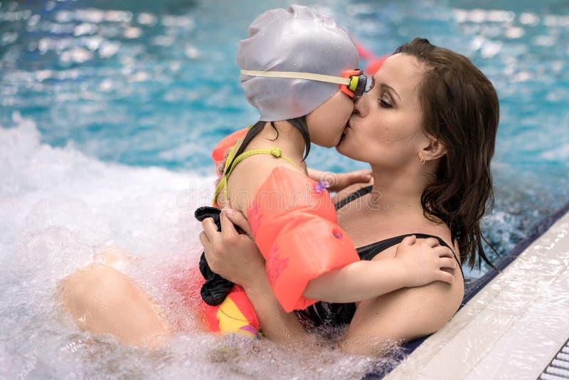 Rodzinny kąpanie, potomstwo matka całuje jej córki fotografia royalty free