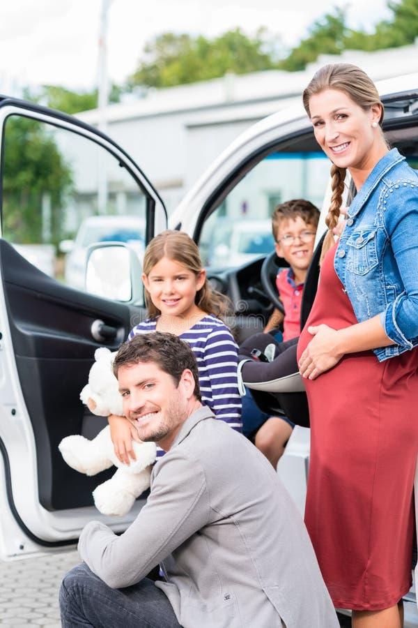 Rodzinny kupienie samochód, matka, ojciec i dziecko przy przedstawicielstwem handlowym, zdjęcie stock