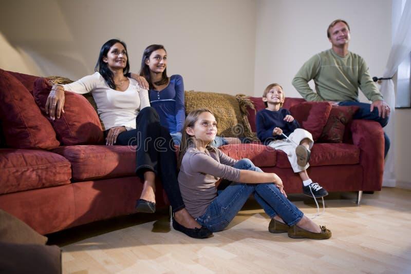 rodzinny międzyrasowy siedzący kanapy tv dopatrywanie fotografia royalty free