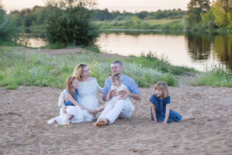 Rodzinny obsiadanie na piasku rzeką obraz royalty free