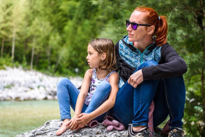 Rodzinny obsiadanie na rzeki skale po natury wycieczkować obrazy stock
