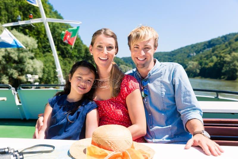Rodzinny obsiadanie szczęśliwie na łodzi na rzecznym rejsie w lecie obraz royalty free
