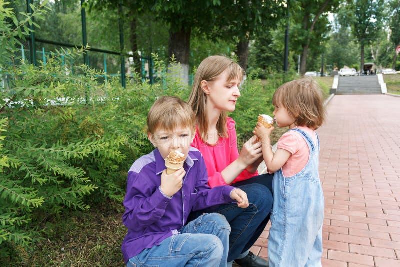 Rodzinny obsiadanie w lato parka łasowania lody obraz stock