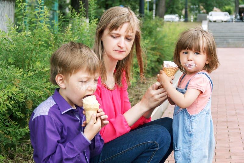 Rodzinny obsiadanie w lato parka łasowania lody obrazy stock