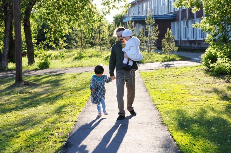 Rodzinny odprowadzenie w parku ojciec z córkami przy słonecznym dniem tata i dziewczyny spaja związek obraz stock