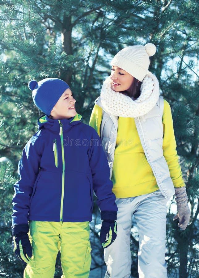 Rodzinny odprowadzenie w zima dniu, szczęśliwej matce i dziecko synu, ubierał w jaskrawym sportswear nad choinką wpólnie fotografia stock
