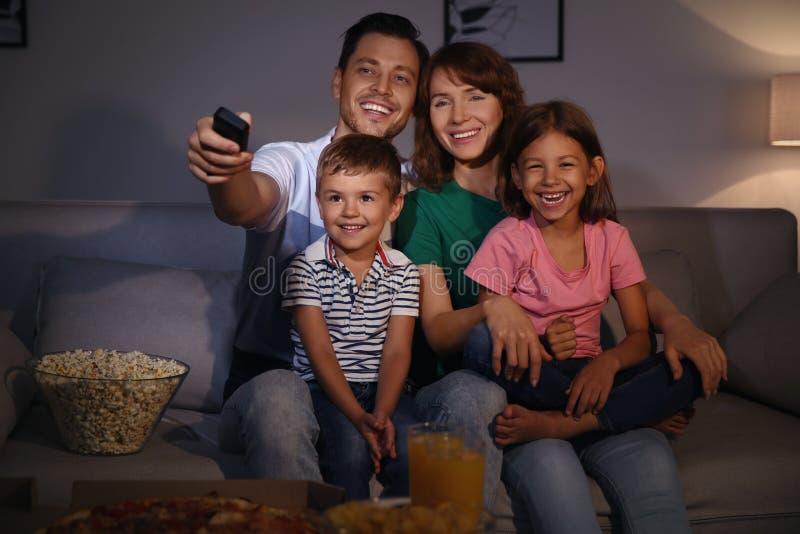 Rodzinny ogląda TV w pokoju przy czasem obraz royalty free