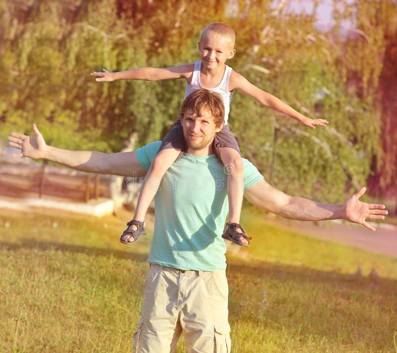 Rodzinny ojca syna i mężczyzna chłopiec obsiadanie na ramion bawić się Plenerowy zdjęcie stock