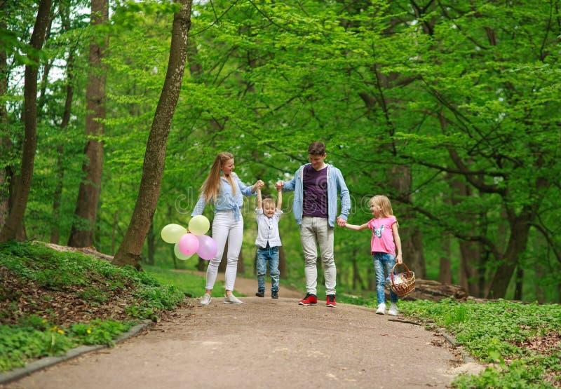 Rodzinny ojciec i matka z dwa dzieciakami chodzi w lato zieleni miasta parku na pinkinie, szcz??liwych wakacji rodzicach i dzieci obraz royalty free
