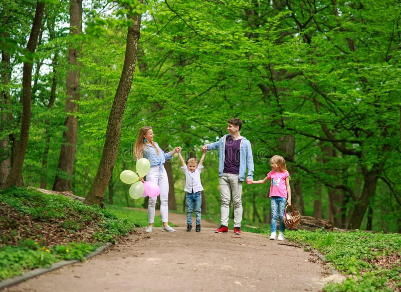 Rodzinny ojciec i matka z dwa dzieciakami chodzi w lato zieleni miasta parku na pinkinie, szcz??liwych wakacji rodzicach i dzieci fotografia royalty free