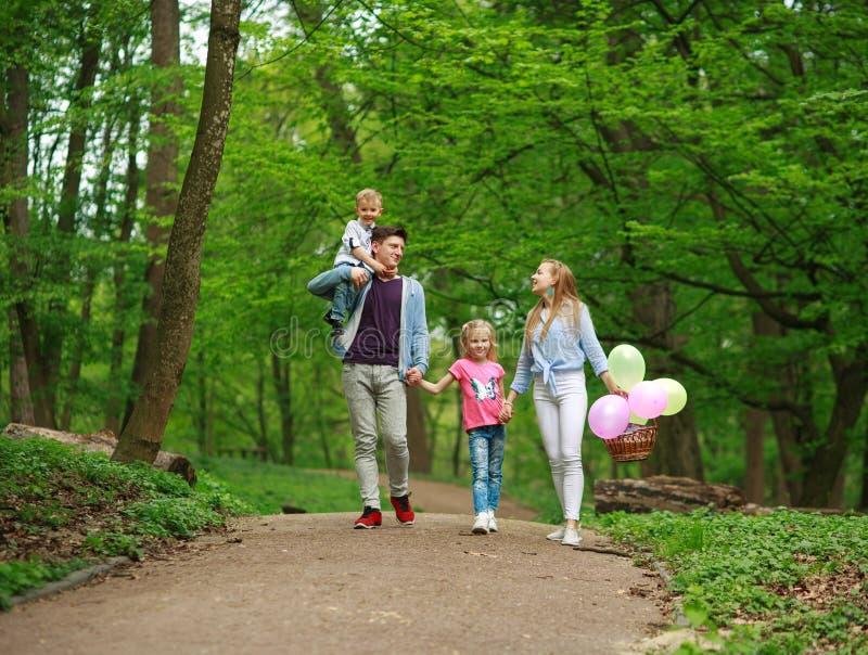 Rodzinny ojciec i matka z dwa dzieciakami chodzi w lato zieleni miasta parku na pinkinie, szcz??liwych wakacji rodzicach i dzieci obrazy stock