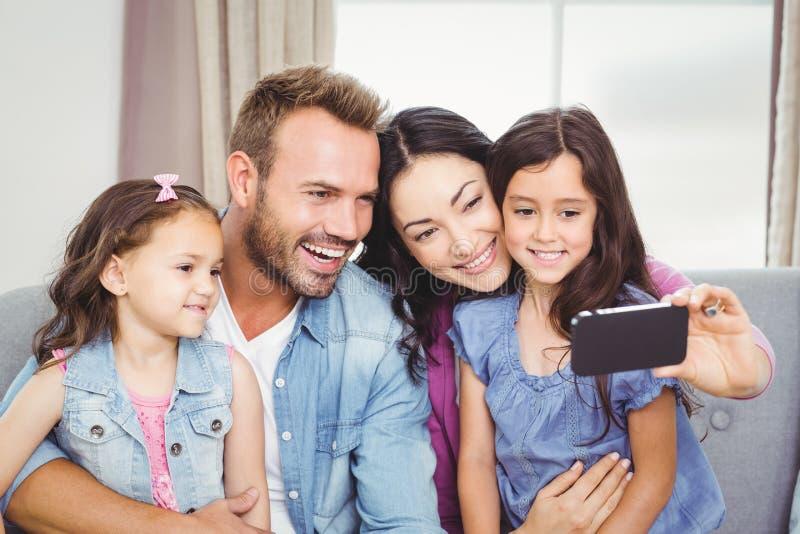 Rodzinny ono uśmiecha się podczas gdy brać selfie na telefonie komórkowym obrazy royalty free