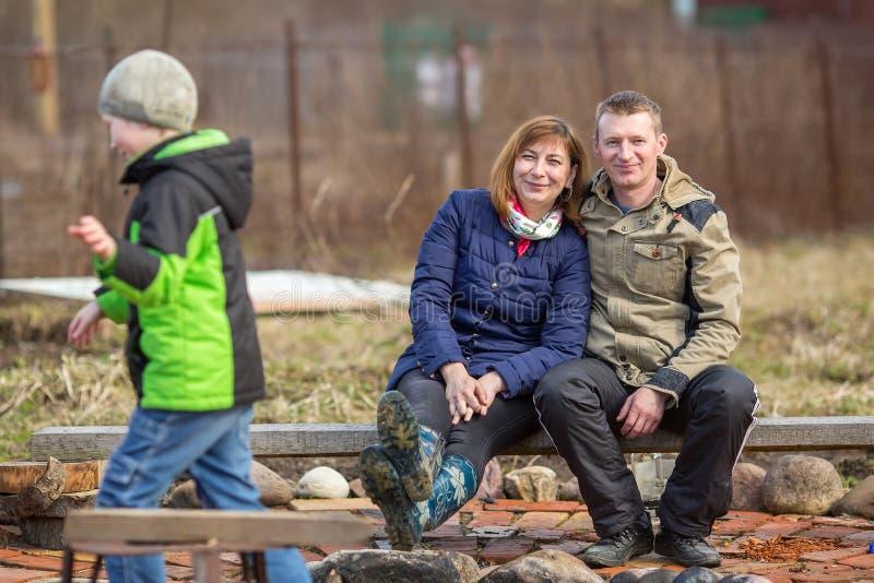 Rodzinny pary obsiadanie na zewnątrz miasto pozy dla kamery obraz royalty free