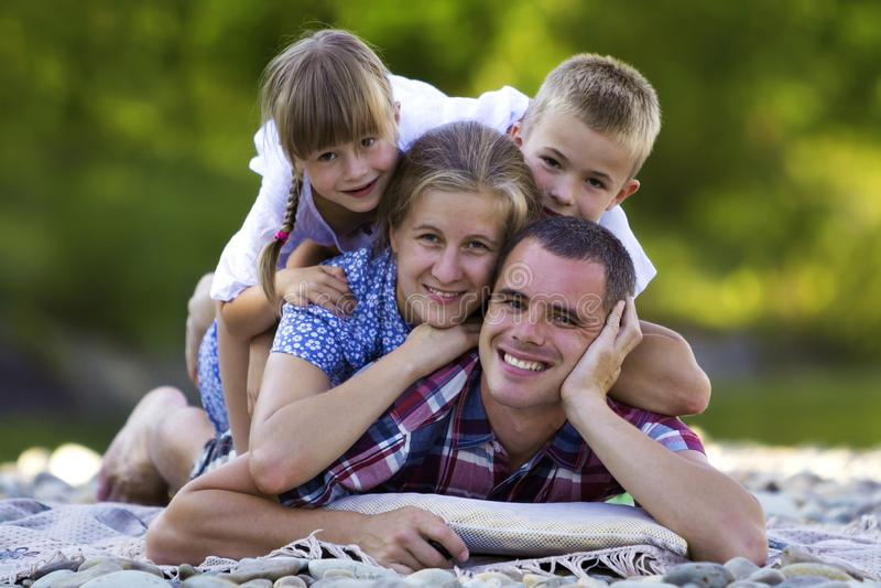 Rodzinny portret młoda szczęśliwa matka, ojciec, dwa ślicznego blond dziecka, chłopiec i dziewczyna na jaskrawym letnim dniu z zi obraz royalty free