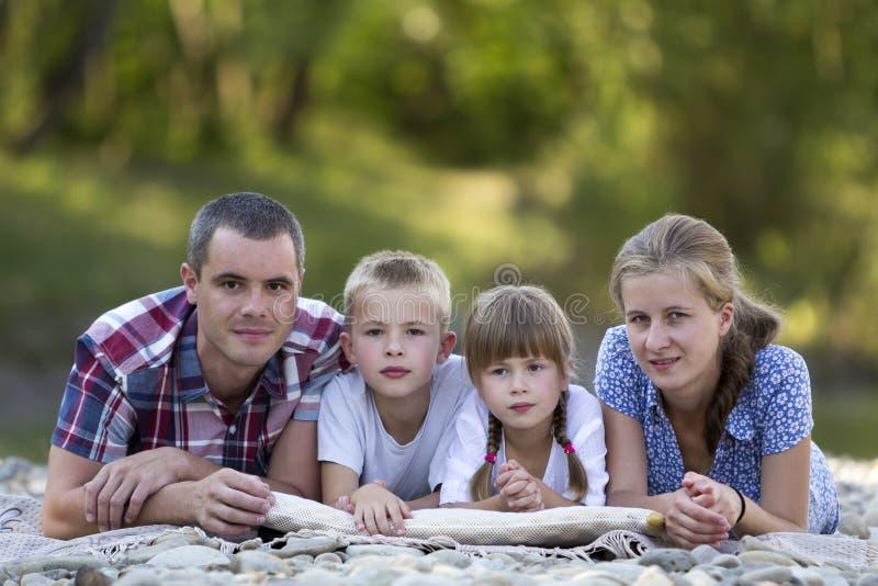 Rodzinny portret młoda szczęśliwa matka, ojciec, dwa ślicznego blond dziecka, chłopiec i dziewczyna na jaskrawym letnim dniu z zi zdjęcie royalty free