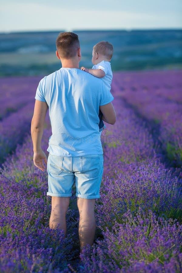 Rodzinny portret ojca mienia dziecka syn pozuje na lawenda śródpolnych jest ubranym niebieskich dżinsach koszulce i zdjęcia royalty free