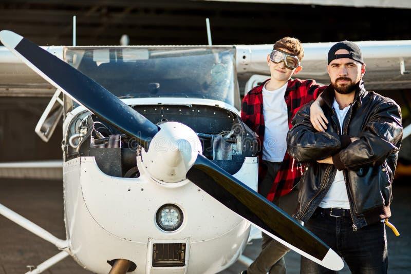 Rodzinny portret tata i syn, stoi wpólnie blisko samolotu na zewnątrz hangaru budynku obraz royalty free